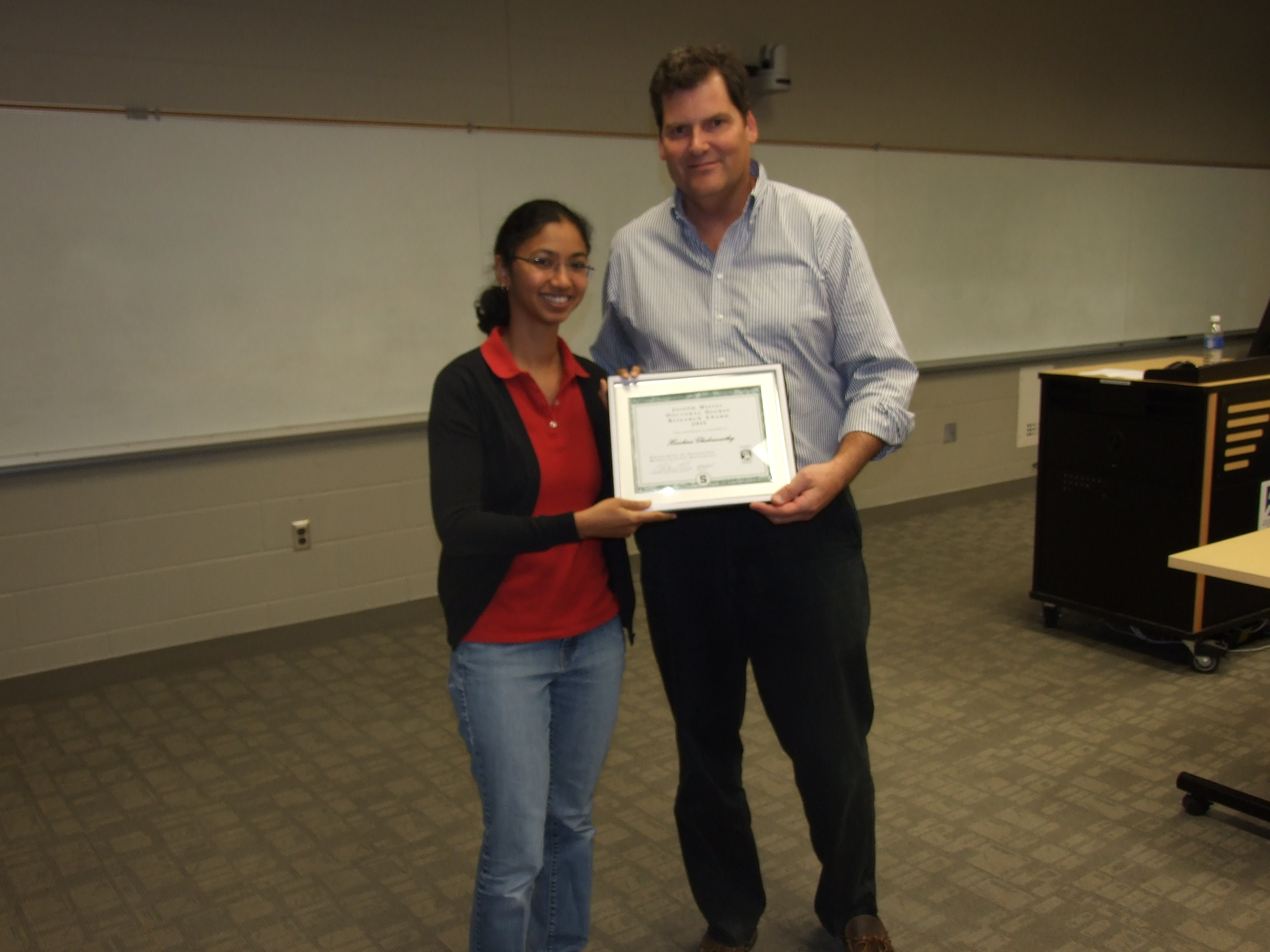 Harshini Chakravarthy receiving an award from Dr. C. Lee Cox